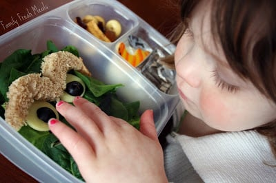 small child looking at Oscar the Grouch lunchbox