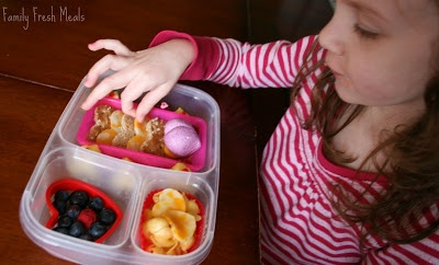 Child sitting at a table eating heart shaped food from lunchbox