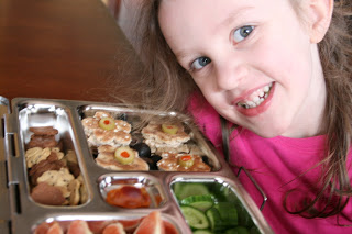 child sitting at a table smiling with planet box lunch box