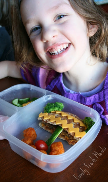 Child smiling, sitting at a table with Potted Plant Lunchbox