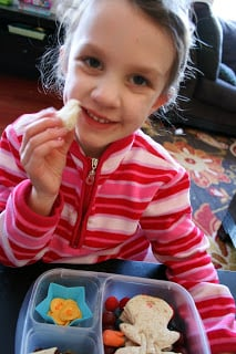 Little girl sitting with The Tooth Fairy Lunchbox, smiling