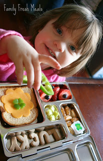 Child sitting at a table with lucky lunch box