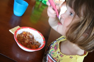 small child sitting at a table eating Crockpot Irish Stew
