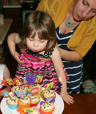 woman holding child while she blows out candles on cupcakes