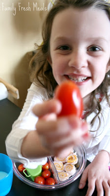 child holding up a cherry tomato to the camera
