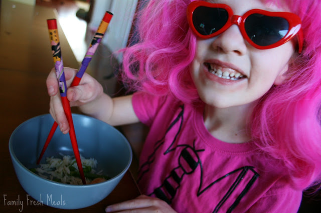 child in a pink wing and sun glasses, eating Coconut Basmati Rice Shrimp with chopstick