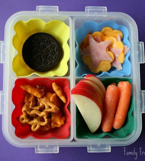 Top down image of square lunchbox with cookies, fruit, vegetables, pretzels, ham and cheese