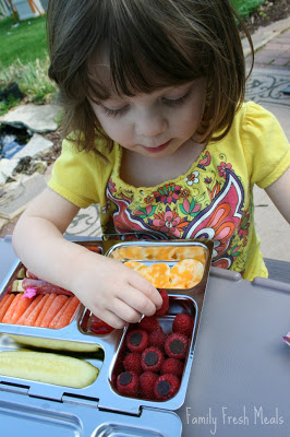 child sitting at a picnic table eating the Antipasto Lunchbox