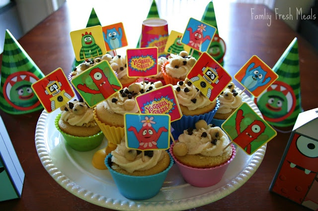 Chocolate Chip Cookie Dough Cupcakes on a serving plater, decorated with Yo Gabba Gabba food picks