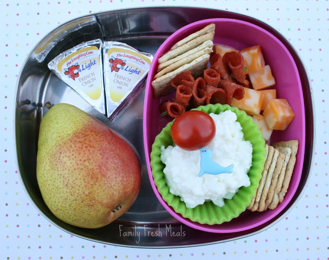 Top down image of a lunch box with a pear, cheese, crackers and pepperoni