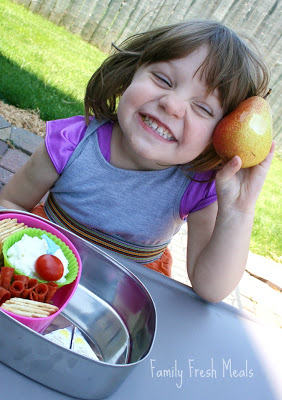 child sitting at a table with lunchbox and holding a pear
