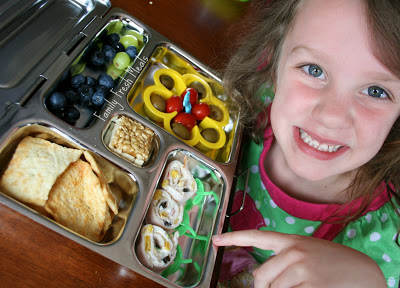 Child sitting at a table with flower themed lunchbox