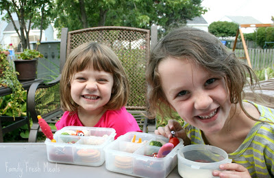 2 children sitting and smiling with Panda Bear lunchboxes