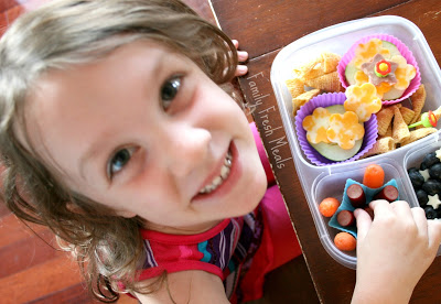 child sitting at table with lunchbox