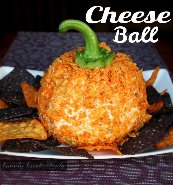 The Perfect Fall Cheese Ball served on a plate with orange and blue tortilla chips