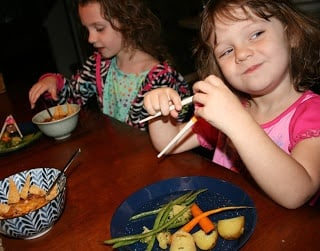 two children sitting at a table eating roasted vegetables