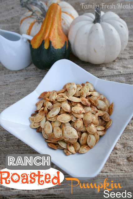 Ranch Roasted Pumpkin Seeds served in a white bowl with small gourds in the background