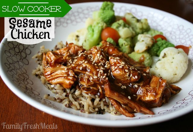 Slow Cooker Sesame Chicken served on a white plate over brown rice, with a side of vegetables