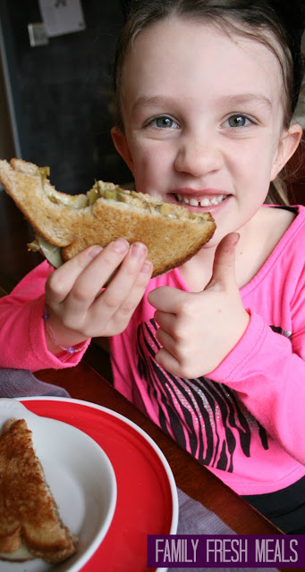 girl holding Green Bean Casserole Grilled Cheese sandwich, giving a thumbs up