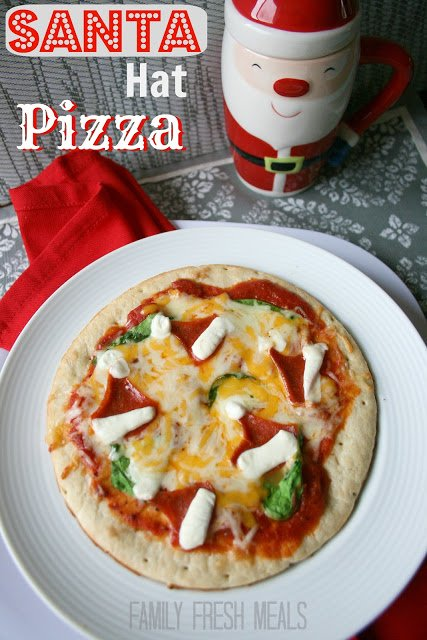 Santa Hat Christmas Pizza on a white plate with a Santa cup in the background
