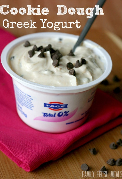 cookie dough greek yogurt in Fage yogurt container topped with mini chocolate chips and a spoon
