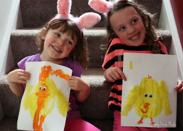 2 children sitting on stairs with bunny ears, holding spring art craft