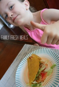 Child sitting at a table with a Chinese Chicken Taco, giving a thumbs up