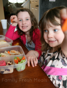two children sitting at a table with lunchboxes