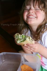 Child smiling, holding a Healthy Avocado Yogurt Chicken Salad pita pocket