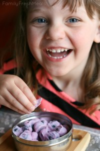 Child smile while eating Frozen Yogurt Covered Blueberries