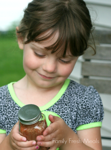 Child holding a jar of the Best Burger and French Fry Seasoning