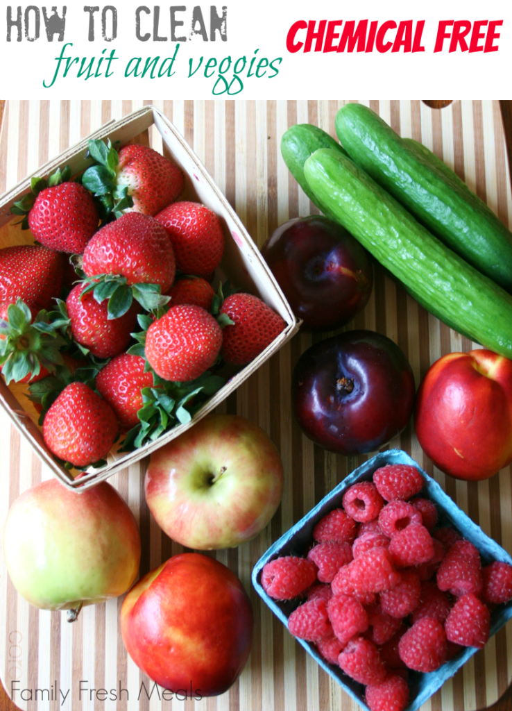 strawberries, raspberries, cucumbers, apples and plums on a cutting board