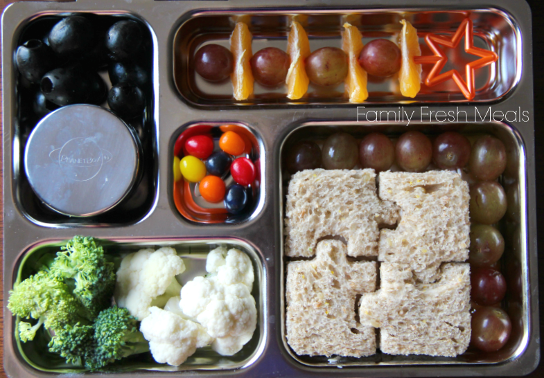 top down picture of a metal lunchbox packed with a variety of finger foods