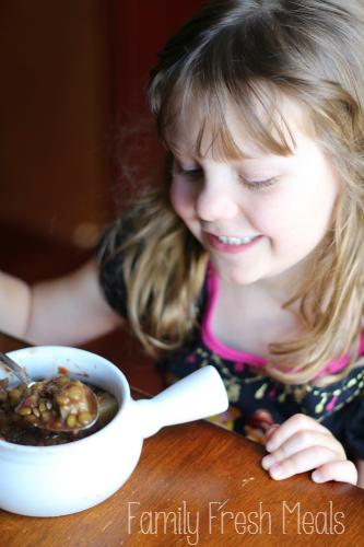 child eating a bowl of lentil soup