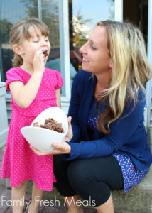woman holding a bowl of Butterfinger Muddy Buddies in a white bowl with a child eating some chex mix.