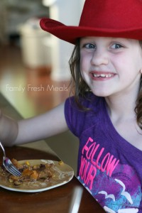 child sitting at table eating cowboy casserole