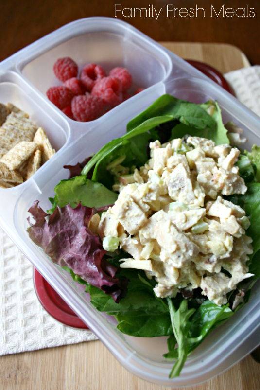 Curried chicken salad on a bed of lettuce, raspberries and some mini wheat cracker - packed in a lunchbox