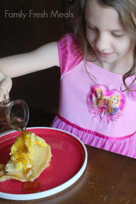 Child pouring syrup over breakfast casserole
