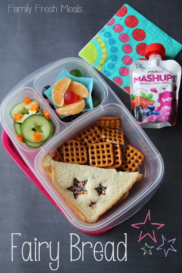 Top down image of a school lunchbox - half sandwich, cucumbers, pretzels, orange slices and gummies