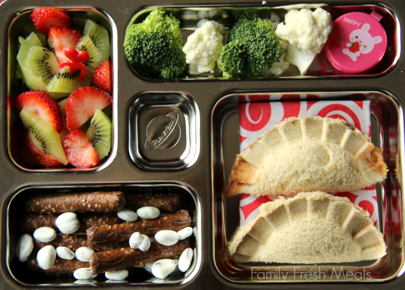 Top down image of a school lunch packed with PB&J dumpling press sandwich, broccoli & cauliflower with small container of dip, kiwi and strawberries, pretzels and yogurt covered raisins.