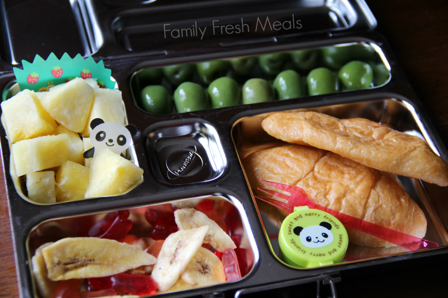 School lunch packed with 2 mini croissants, a small container of jelly, olives, pineapple, banana chips and some fruit snacks.