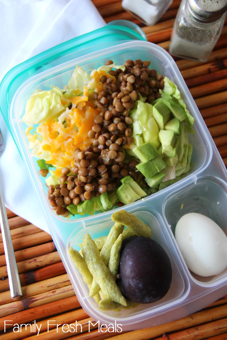 Lunchbox packed with a salad, hard boiled egg, plum and peapod chips