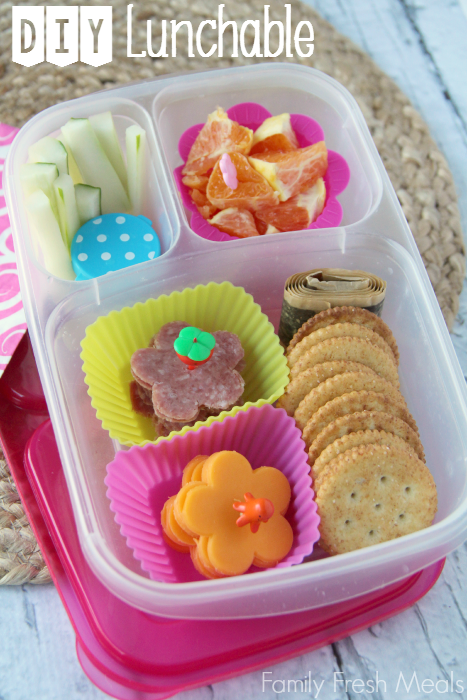 lunch meat and cheese flowers, crackers, fruit leather, oranges, cucumbers and a container of dip. Packed in a lunchbox