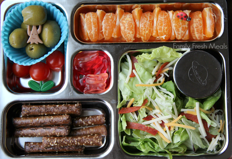 salad with a container of dressing, oranges, pumpernickel pretzels, cherry tomatoes, olives and some fruit snack bunnies for dessert. Packed in a metal lunchbox