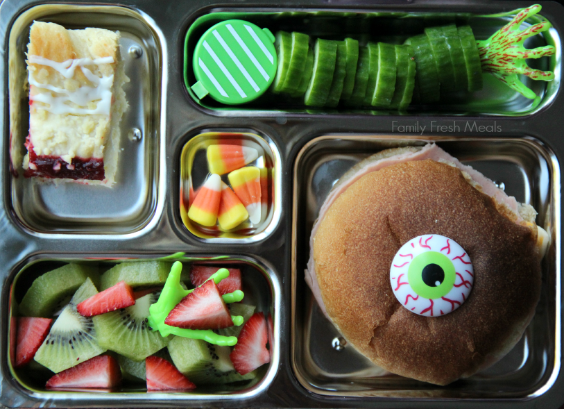 There is a turkey and cheese sandwich, cucumbers and a container of dip, small piece of leftover coffee cake, fresh strawberries & kiwi and some candy corn. Packed in aPlanetbox lunchbox
