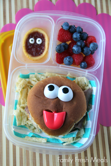 Ham and cheese sandwich, crunchy tortilla strips, fresh blueberries and strawberries, and a cookie (with candy eyes) for dessert. Packed in a lunchbox