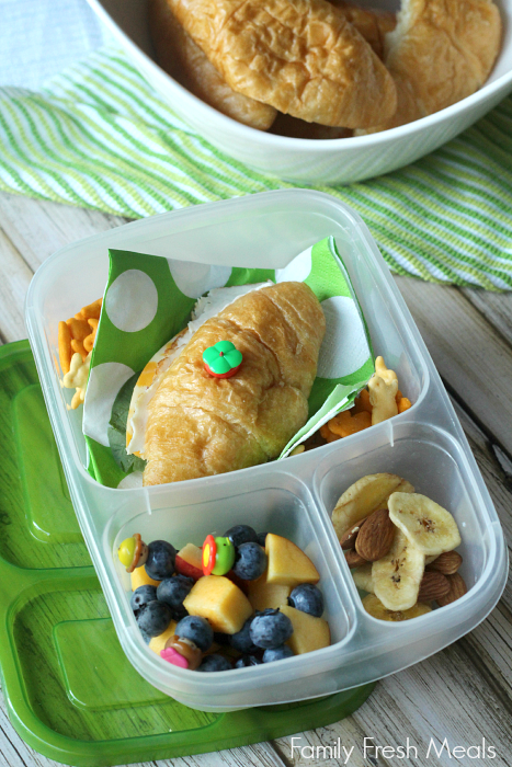 deli sandwich on a croissant,  bunny crackers, fresh blueberries and peach, and an almond/banana chip mix - packed in a lunchbox