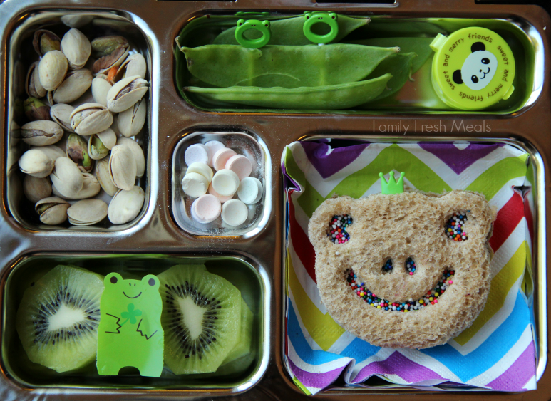pistachios, snap peas with a container of dip, a frog shaped sandwich, kiwi and a couple candies packed in a metal lunchbox