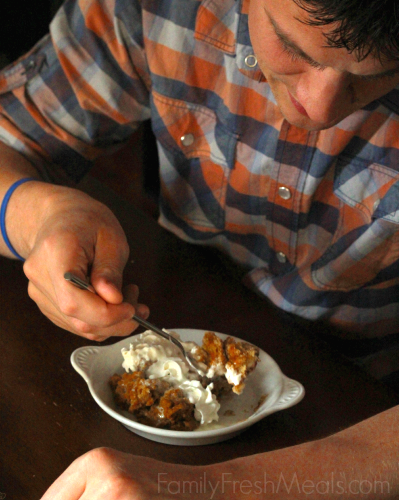 man sitting at a table eating pumpkin pie