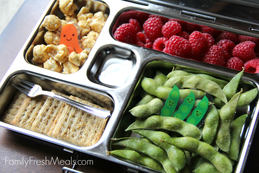 PlanetBox packed with fresh raspberries, caramel corn, crackers and steamed edamame.